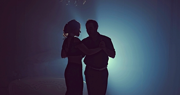 Couple dancing romantic tango at night. Silhouette couple ballroom. Smoke